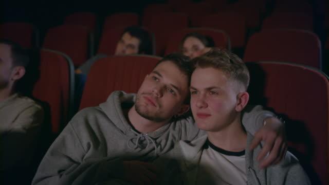 Paar-Homosexuell-umarmen-im-Kino-Homosexuelle-Männer-umarmen-im-Kino