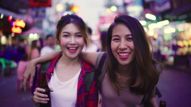 Reisender-Backpacker-asiatische-Frauen-Lesben-LGBT-paar-Reisen-in-Bangkok-Thailand-Weiblich-trinken-Alkohol-oder-Bier-an-der-Khaosan-Road-die-berühmteste-Straße-in-Bangkok-