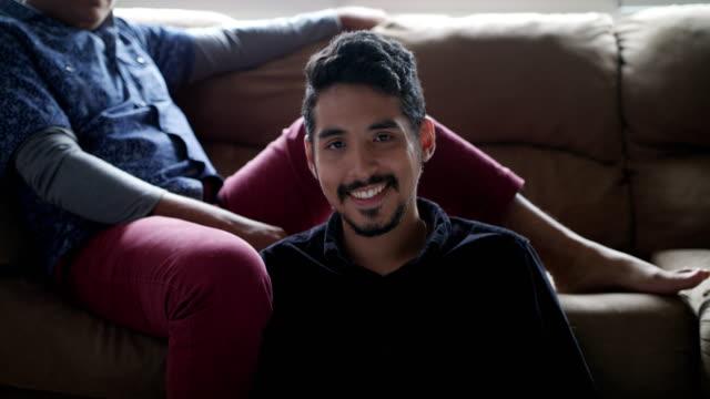 Hispanic-Gay-paar-Holding-Hands-On-Sofa-zu-Hause