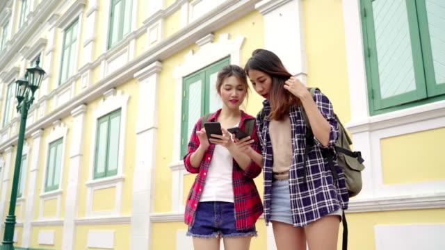 Reisender-Backpacker-asiatische-Frauen-Lesben-LGBT-paar-Reisen-in-Bangkok-Thailand-Glückliche-junge-weibliche-Richtung-und-auf-der-Suche-Lageplan-auf-Smartphone-