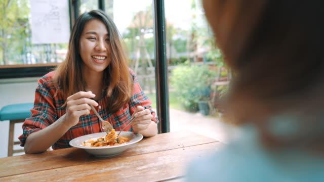 Pareja-de-lesbianas-lgbt-hermosa-mujer-asiática-feliz-sentado-cada-lado-comiendo-un-plato-de-espagueti-italiano-mariscos-y-papas-fritas-en-el-restaurante-o-cafetería-mientras-que-sonreír-y-mirar-la-comida-