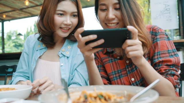 Glücklich-schöne-asiatische-Freunde-Frauen-Blogger-Smartphone-Fotos-und-Lebensmittel-Vlog-video-für-ihre-Abonnenten-und-ihrem-Kanal-im-Café-