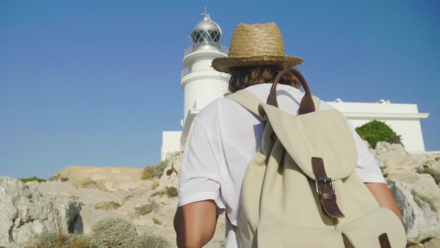 Portrait-of-a-beautiful-young-tourist-(girl)-looks-at-an-lighthouse-with-a-backpack-in-a-straw-hat-a-white-house-backdrop-