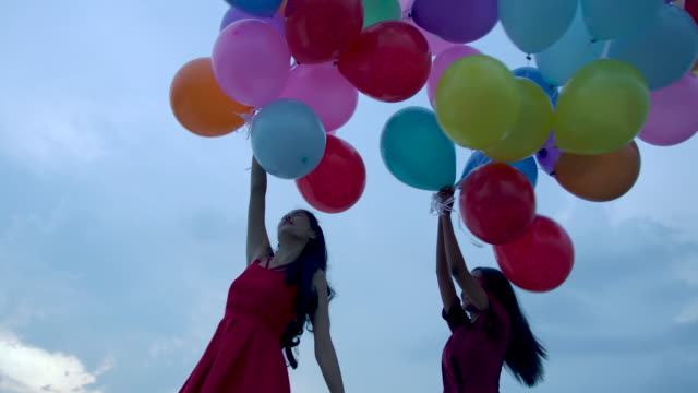 Two-girls-holding-balloon-with-sky-background-in-slow-motion-