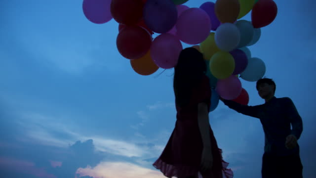Young-couple-people-holding-balloon-with-sunset-background-in-slow-motion-