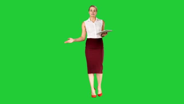 Mujer-de-negocios-con-tablet-caminando-y-hablando-con-la-cámara-en-una-pantalla-verde-Chroma-Key