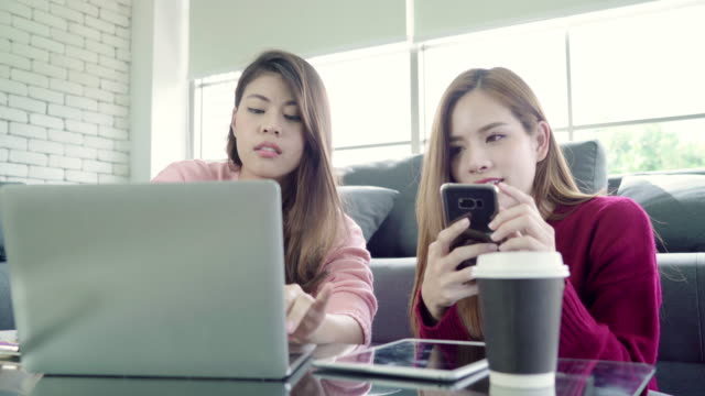 Lesbian-Asian-couple-using-laptop-making-budget-in-living-room-at-home-sweet-couple-enjoy-love-moment-while-lying-on-the-sofa-when-relax-at-home-Lifestyle-couple-relax-at-home-concept-