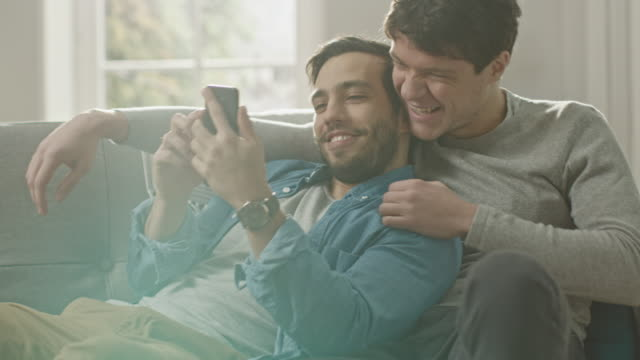 Süße-männliche-Gay-paar-verbringen-Zeit-zu-Hause-Sie-sind-unten-auf-dem-Sofa-liegen-und-ein-Smartphone-benutzen-Stöbern-sie-Online-Partners-Hand-ist-um-seine-Geliebte-Sie-Lächeln-und-lachen-Zimmer-ist-Modern-eingerichtet-