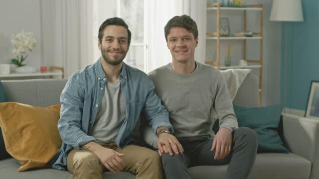 Nette-attraktive-männliche-Gay-paar-sitzen-zusammen-auf-dem-Sofa-zu-Hause-Freund-legt-seine-Hand-auf-die-Verlobten-Sie-sind-glücklich-und-Lächeln-Sie-sind-lässig-gekleidet-und-ihre-Zimmer-ist-Modern-eingerichtet-