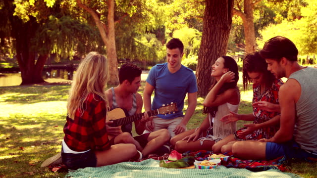 Happy-friends-in-the-park-having-picnic-and-playing-guitar