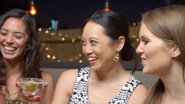 Female-Friends-Enjoying-Night-Out-At-Rooftop-Bar-Slow-Motion