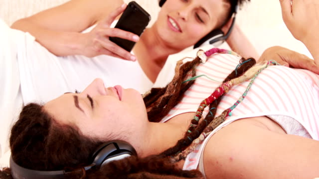 Smiling-lesbian-couple-listening-music-together