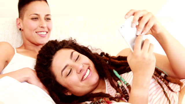 Smiling-lesbian-couple-using-smartphone-together-in-the-bed