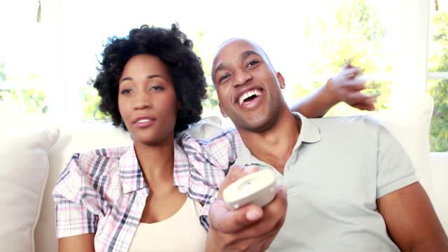 Feliz-pareja-viendo-televisión-en-el-sofá-en-la-sala-de-estar