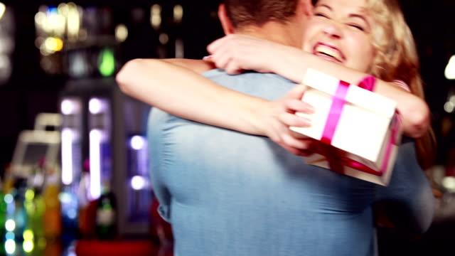 Junges-Paar-umarmen-mit-einem-Geschenk