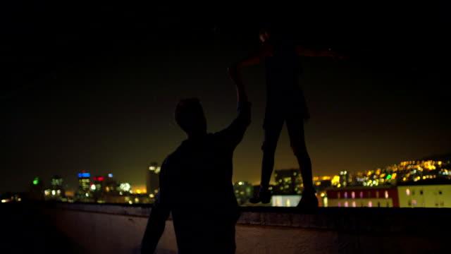 Mann-hält-Hand-mit-Freundinnen-die-auf-einen-Stand-auf-dem-Dach