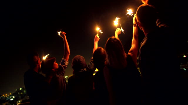 Junge-Freunde-feiern-auf-dem-Dach-mit-Wunderkerzen