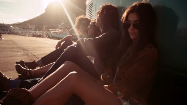 Hipster-Freunde-Ruhen-Sie-sich-in-ihrem-van-während-dem-Sonnenuntergang