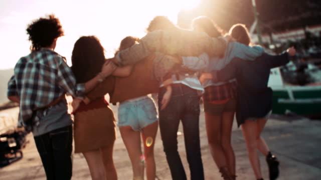 Teen-hipster-amigos-caminando-en-el-Muelle-al-anochecer