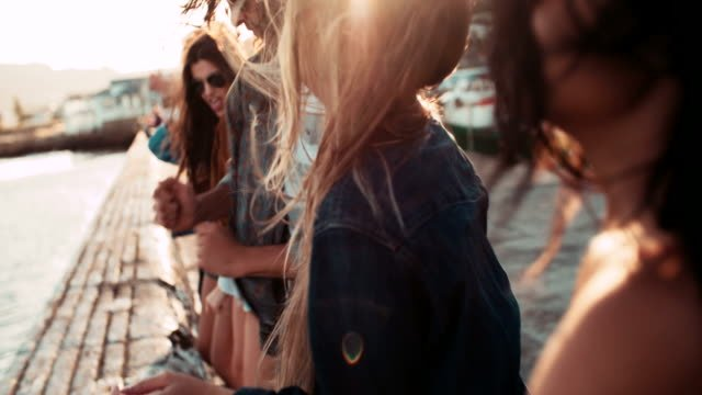 Teenager-hipster-style-friends-dancing-on-the-pier-at-sunset