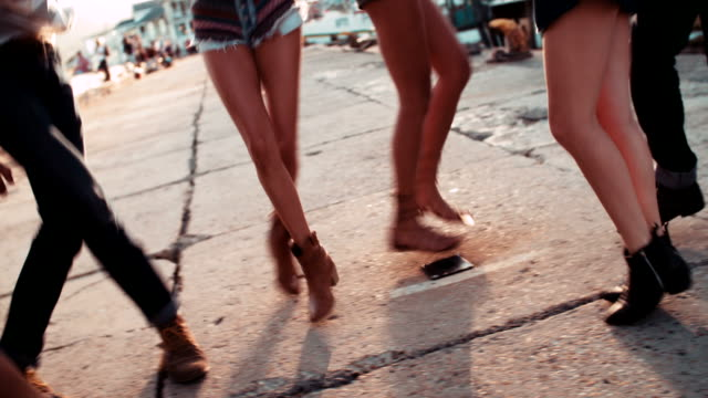 Close-up-of-legs-dancing-at-the-harbor-on-sunset