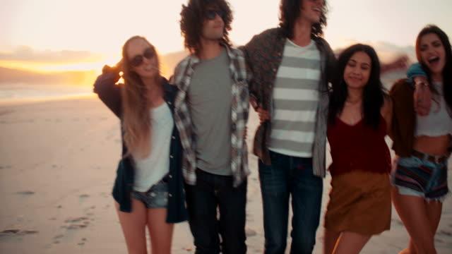 Hipster-amigos-abrazar-con-alegría-al-anochecer-en-junto-al-mar