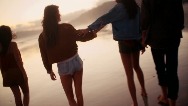 Teen-amigos-disfrutando-de-un-paseo-en-la-playa-en-el-atardecer