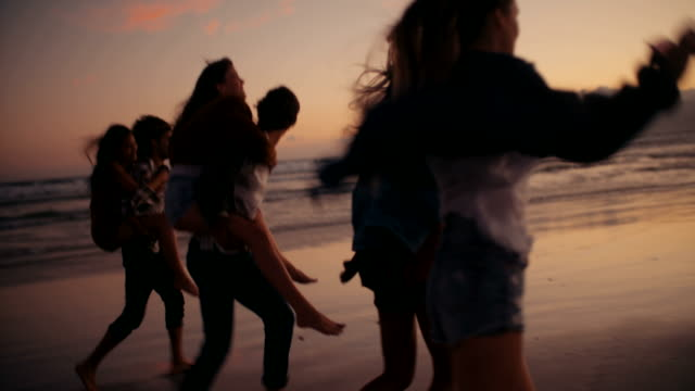 Hipster-friends-doing-funny-piggyback-rides-on-beach
