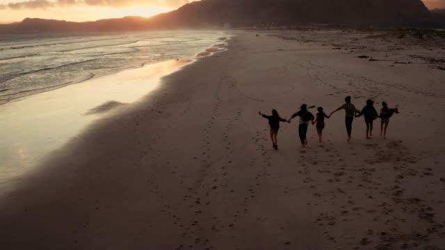 Young-adult-friends-enjoying-a-walk-at-beach-on-sunset