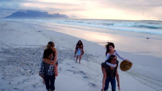 Hipster-amigos-teniendo-divertidos-paseos-superpuesto-sobre-playa-al-anochecer