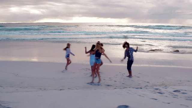 Teen-friends-dancing-on-the-beach-at-sunset