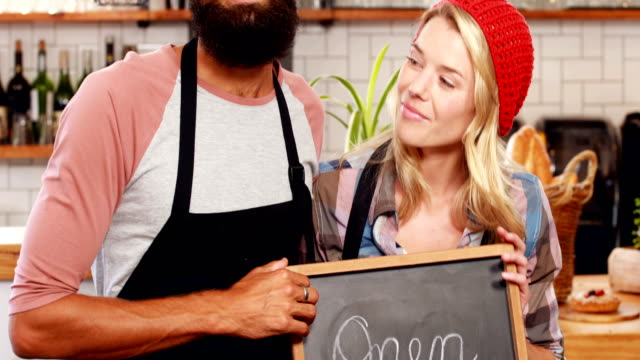 Hipster-couple-holding-open-sign
