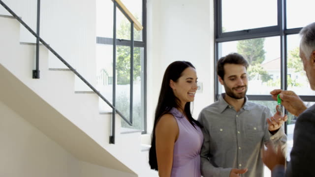 Real-estate-agent-giving-keys-to-couple
