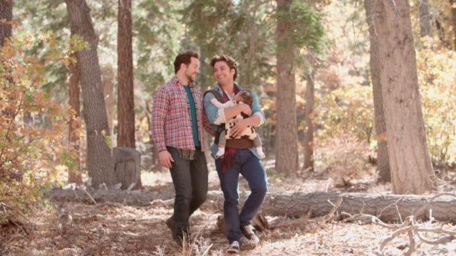 Männliche-Paar-im-Wald-mit-Baby-im-Schlinge-zu-Fuß-im-Richtung-Kamera
