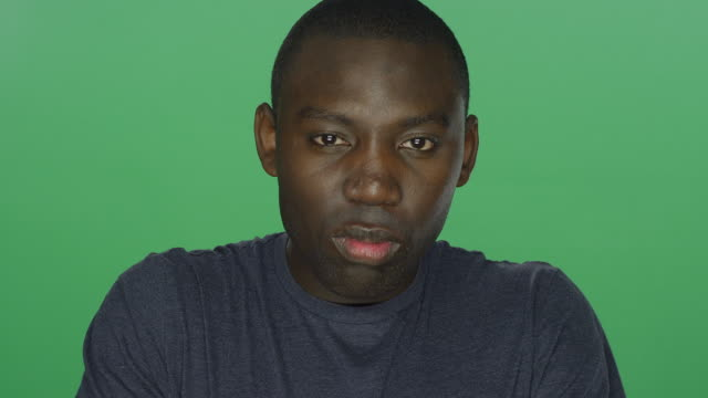 Young-African-American-man-glares-on-a-green-screen-studio-background