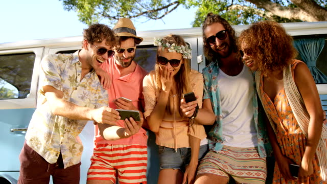 Hipster-friends-looking-at-smartphone-and-laughing