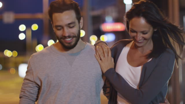 Attractive-Happy-Couple-Walking-on-Streets-of-Night-Town