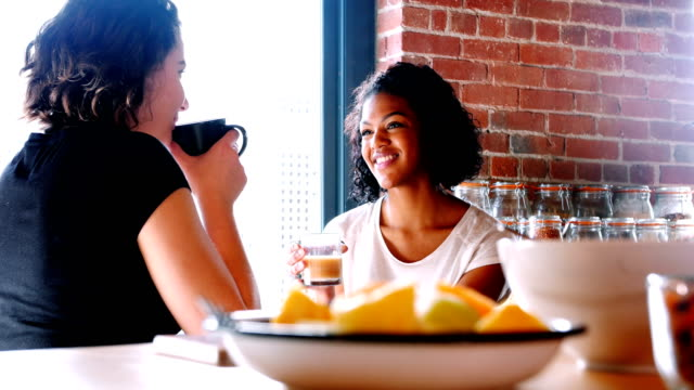 Pareja-de-lesbianas-interactuando-con-otros-desayunando