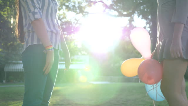 LGBT-girlfriends-stand-together-holding-hands-with-inflatable-balloons-and-bracelet-in-backlight