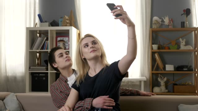 Zwei-junge-schöne-Mädchen-sitzen-auf-der-Couch-und-machen-Selfies-Lesben-LGBT-blond-brünett-60fps