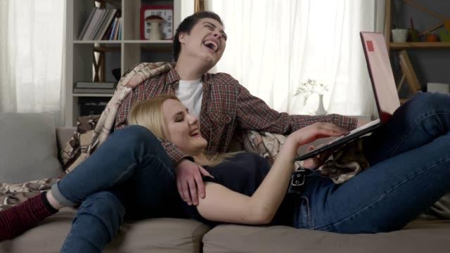 Junge-blonde-Frau-liegt-auf-dem-Schoß-der-eine-Brünette-und-ein-lustiges-Video-auf-Laptop-lachen-Freunde-Lesben-60-fps