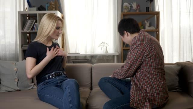 Zwei-junge-lesbische-Mädchen-auf-der-Couch-sitzen-eine-Mädchen-mit-kurzen-Haaren-gibt-ein-Geschenk-für-ihren-Partner-Liebe-ein-neues-Jahr-eine-Überraschung-60fps