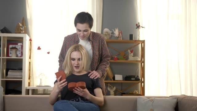Zwei-junge-lesbische-Mädchen-eine-Mädchen-mit-kurzen-Haaren-gibt-einen-Sarg-in-der-Form-eines-Herzens-zu-ihrem-Partner-eine-Blondine-öffnet-den-Sarg-überrascht-60-fps