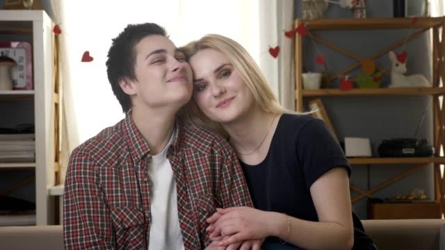 Zwei-junge-lesbische-Mädchen-sitzen-auf-der-Couch-schaut-in-die-Kamera-halten-Händchen-Knuddeln-kuscheln-Liebe-Care-Familienidylle-Lächeln-glücklich-60fps