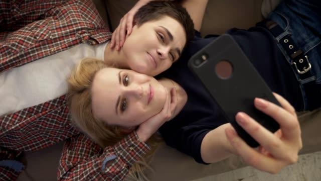 Dos-chicas-jóvenes-mienten-en-el-sofá-hacer-selfie-en-un-teléfono-inteligente-Sonriente-amantes-pareja-joven-lgbt-top-shot-60-fps