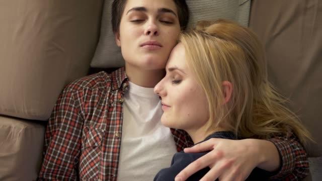 Zwei-junge-lesbische-Mädchen-liegen-auf-der-Couch-Umarmung-kuscheln-schlafen-schaut-die-Kamera-LGBT-Familienkonzept-Top-Shot-60fps-Mädchen-mit-kurzen-Haaren