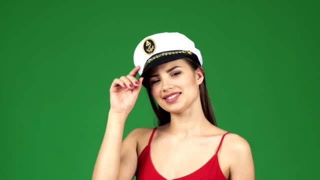 Beautiful-young-sexy-woman-smiling-joyfully-wearing-sailor-cap-on-green-screen