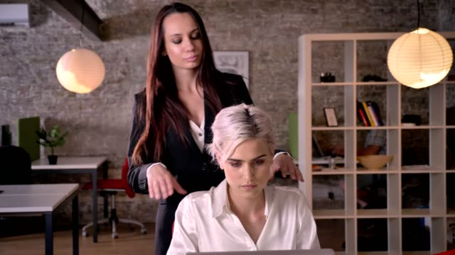 Two-young-lesbians-in-office-beautiful-business-woman-massaging-other-woman-relaxing-and-pleasant