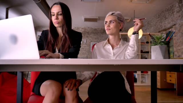 Young-confident-blonde-woman-touching-knee-of-other-woman-in-modern-office-lesbian-concept-sitting-at-table-with-laptop