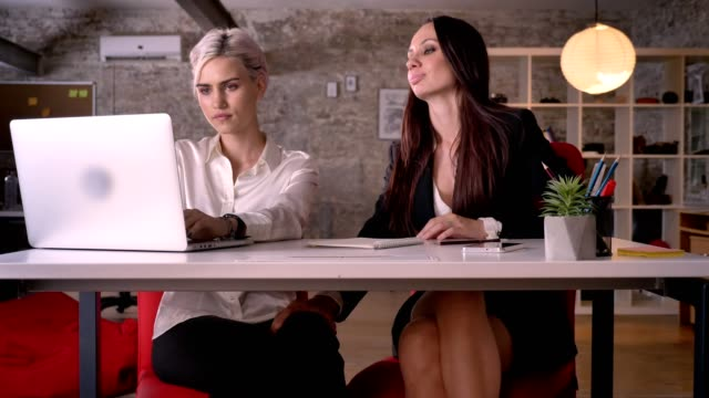 Young-attractive-sexy-women-touching-each-other-under-desk-in-modern-office-lesbian-concept-smiling-happy